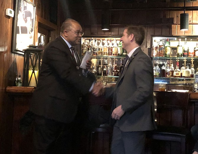Deputy Chief Dave Huchler, right, is congratulated on his retirement from the Alexandria Police Department by former Police Chief Earl Cook, March 27 at Landini Brothers Restaurant. Huchler has been named the new Chief of Police for the Metropolitan Washington Airports Authority.