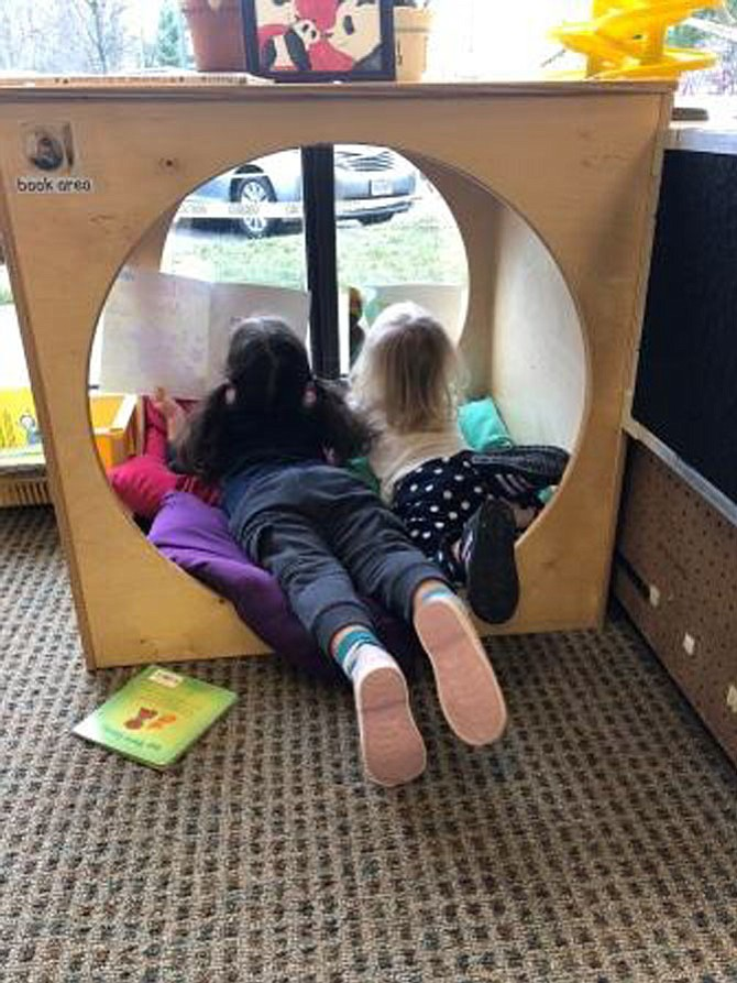 Two children enrolled at the new Robert E. Simon Jr. Children's Center enjoy taking in the sights outside their reading nook.