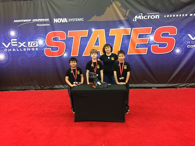 Three students at Aldrin Elementary School in Reston, David Nelson, Connor Uehara and Anthony Starkov, won this year's Vex IQ Robotics Virginia State Championship, elementary school division. They are pictured with the Team Coach, Zina Raye.