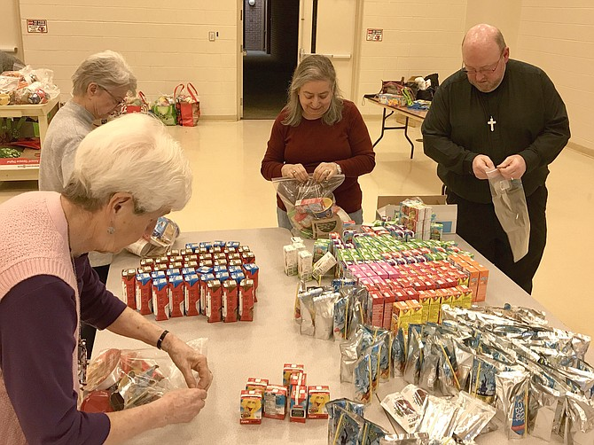 Community members helping prepare Power Packs of Food for Others.