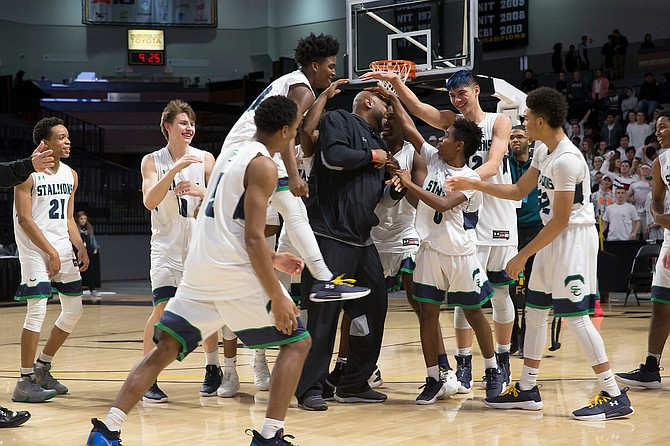 Mike Robinson, Head Coach of South County, is congratulated by his team on the court after their 63-47 6A State Championship win. Robinson was named Coach of the Year.