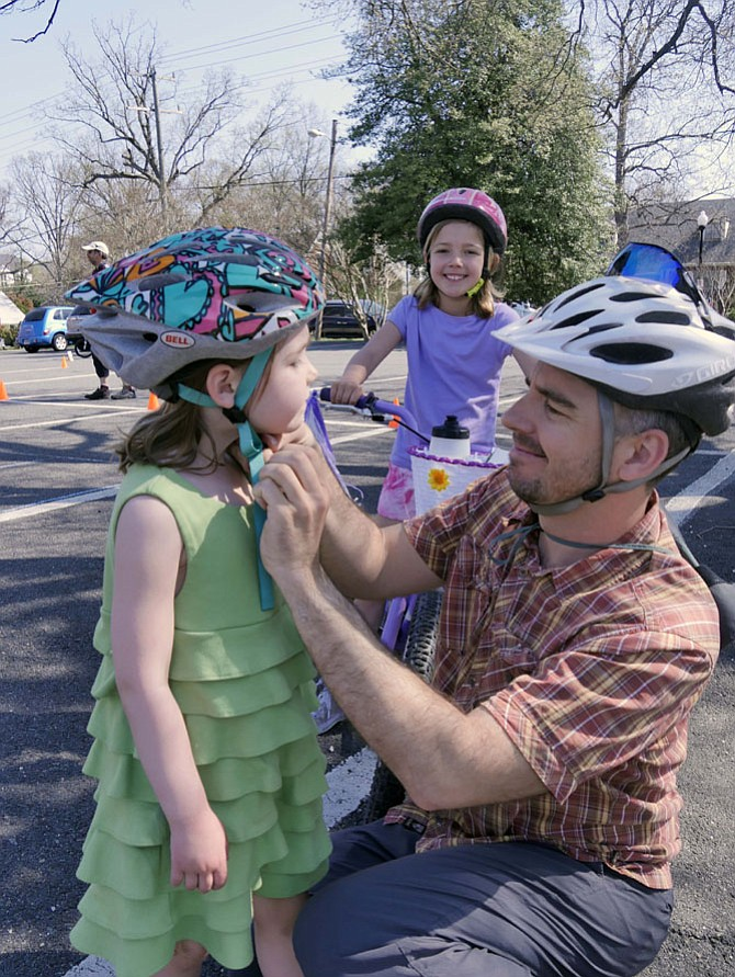 """Five-year-old Anna Oliphant scrunches her face at the Bike Rodeo on Saturday, advising her father the helmet is too tight. """"And I want it to be loose."""" Anna's 7-and-a-half-year-old sister Abigail waits patiently behind her declaring, """"I've been riding around the obstacles. I'm here today because I like bike riding. I think it's fun."""""""