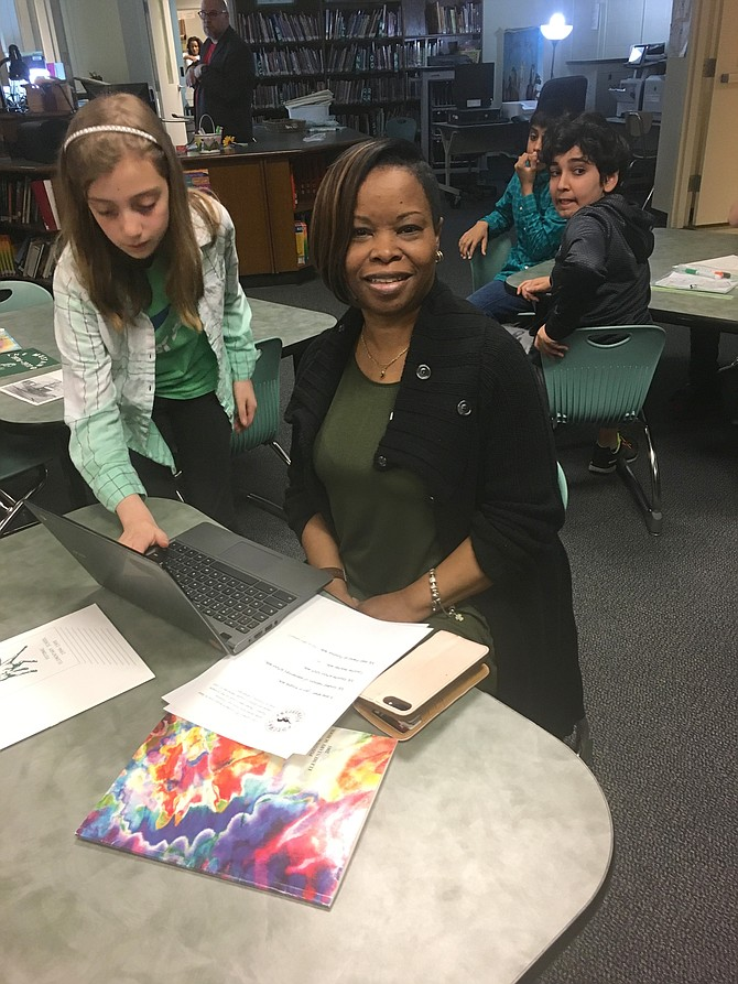 Former student Denise Jackson Johnson records her memories of Potomac Elementary School with the help of fifth grader Sarah Bland on Thursday, April 12.