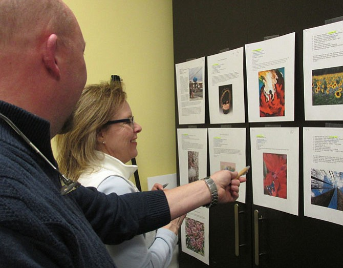 Event planning-committee volunteer Dennis Michael and Britepaths Development Assistant Debra Jones peruse the art submissions.