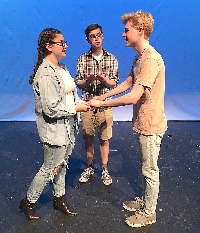 "In Woodson High's ""Our Town,"" Michael Richardson (center) plays the minister marrying sweethearts Emily (Grace Bonaccorsy) and George (Andrew Black)."