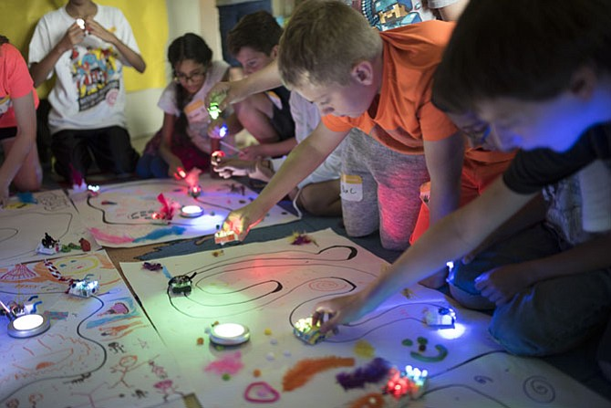 Children at Camp Invention create tracks for a self-driving robot. This camp has funding to sponsor low-income children this summer.