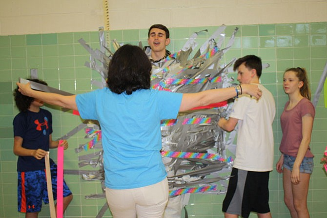 Assistant Principal Cherith Pierson donates her money in order to help stick eighth grader Matt Harlow to the wall.