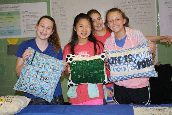 From left: Katie Mahony, Sabrina Chang, Leah Connell and Ellie Mcfadden showcase their stitched pillows that they have been working on for months to their friends and family.
