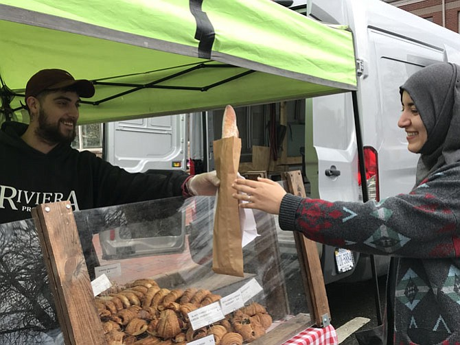Maryam Heidari of Reston is the first customer at Opening Day for the 2018 Herndon Farmers Market.