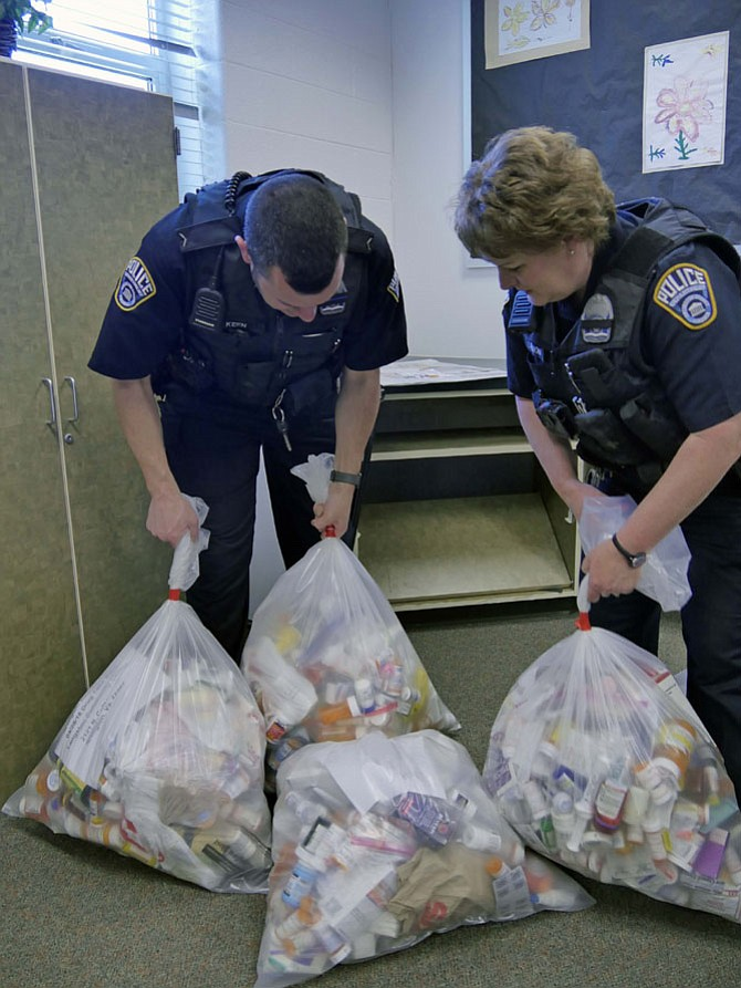 Corporal Beth Lennon and Officer Mike Keen pile up bags filled with discarded prescription drugs at the Langston Community Center drop off location on Saturday, April 28.
