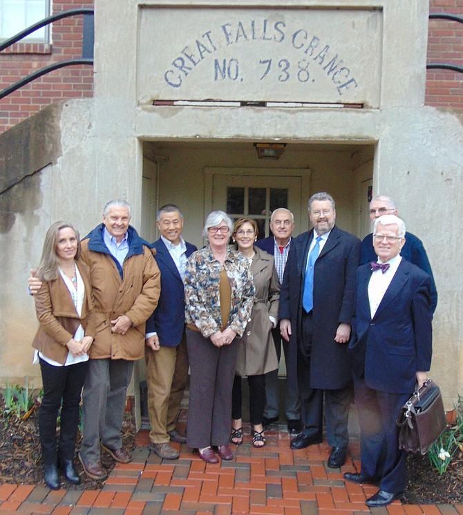 Standing in front of the Great Falls Grange are community leaders (from left): Suzanne Pidgeon, Jorge Adeler, Gary Pan, Linda Jones, Linda Thompson, Glen Sjoblom, G. Stephen Dulaney, Eric Knudsen, and John McGeehan.