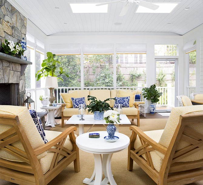 Kelley Proxmire suggests using plants and planters in a variety of sizes — such as these blue and white ceramic pots, to create a light and airy patio space.