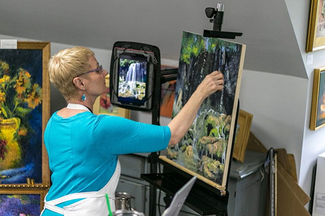 Donna Robinson working on a waterfall painting during the festival.