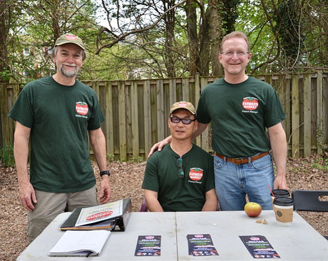 "Your McLean Farmers Market welcoming committee. Standing, from left: market manager, Bob Baldwin and assistant manager Bill Smith; seated, Yong Gong, a recent, temporary transplant from South Korea, and self-described ""assistant to the assistant."" Together they run the show, helping vendors and visitors alike."