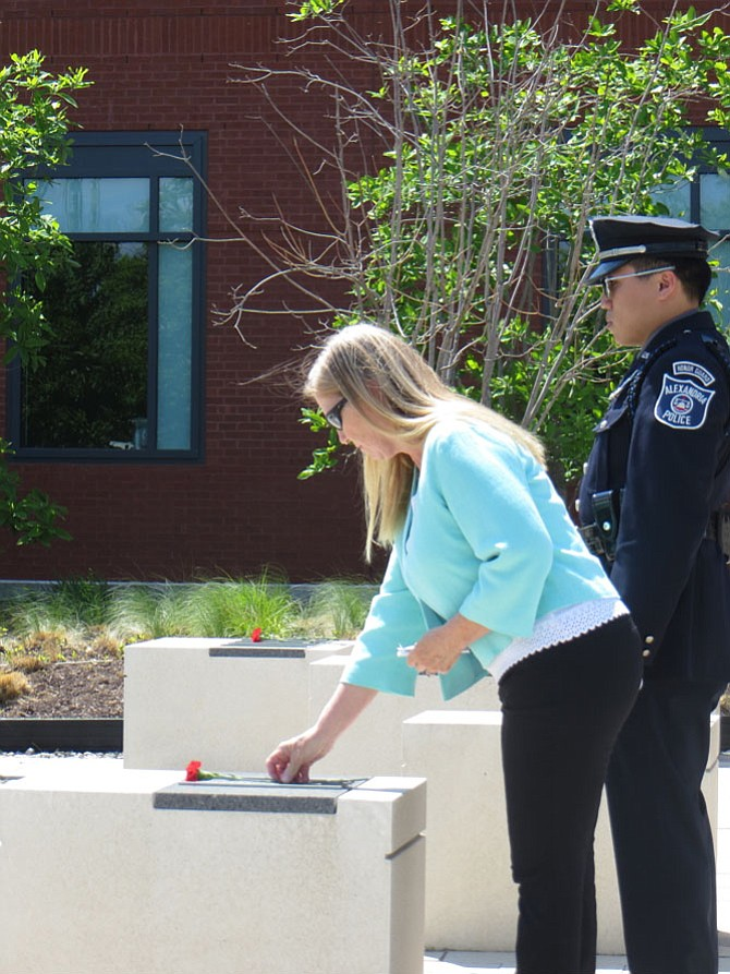 Judy Birney Schoenle lays a flower at the memorial for her father, Conrad Birney, killed in 1972 responding to a bank robbery.