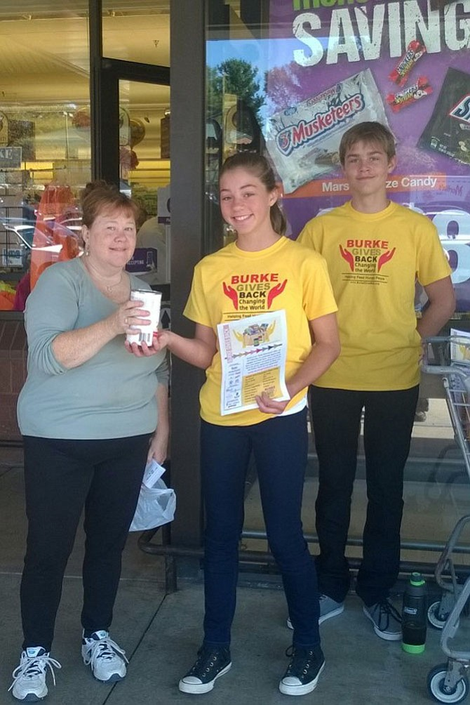 "Maggie Waldron of Burke gives a 26-ounce can of chicken noodle soup Oct. 21, 2017 to Chloe Charlesworth, 12, and her brother Spencer, 14, in front of the Giant Food grocery store at the Burke Town Center. The Lake Braddock Secondary School students volunteered last fall for the ""Burke Gives Back: Changing the World"" teams at three grocery stores along Burke Centre Parkway between Ox and Old Keene Mill roads. Burke residents can shop again at these stores  May 19 from 9 a.m. to 1 p.m. and help keep 400 local children from going hungry this summer in Fairfax County. Grocery lists will be distributed at the entrances of Safeway at 5727 Burke Centre Parkway, Giant Food at 6011 Burke Centre Parkway and the Safeway at 9596 Old Keene Mill Rd."