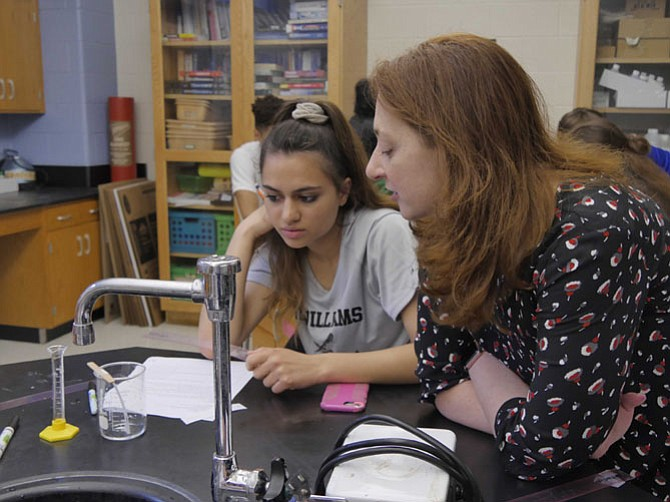 Jennifer Kazanciyan helps honors chemistry students at T.C. WIlliams solve a mystery through chromatography, the separation of black into different colors.