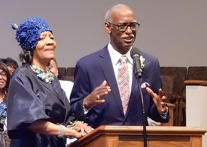 June Johnson stands beside her husband, the Rev. Eugene Johnson, while he addresses the congregation.