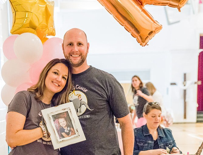 Mike and Lindsay Rhoades hold a photograph of their daughter, Kate, who was diagnosed with acute lymphoblastic leukemia and died when she was just 4 years old.