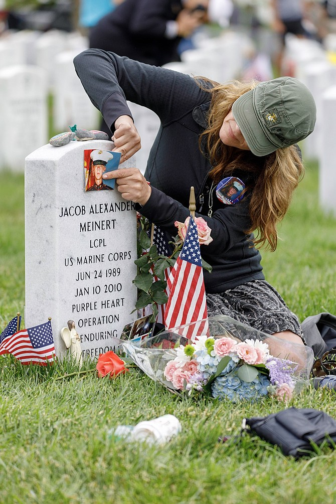 Randi Meinert of Racine, Wisc., places a photo of her brother Jacob on his headstone in Section 60 of Arlington National Cemetery following the Memorial Day ceremonies May 28. Lance Corporal Jacob Meinert was killed Jan. 10, 2010, when he stepped on a land mine while serving with the U.S. Marines in Afghanistan.