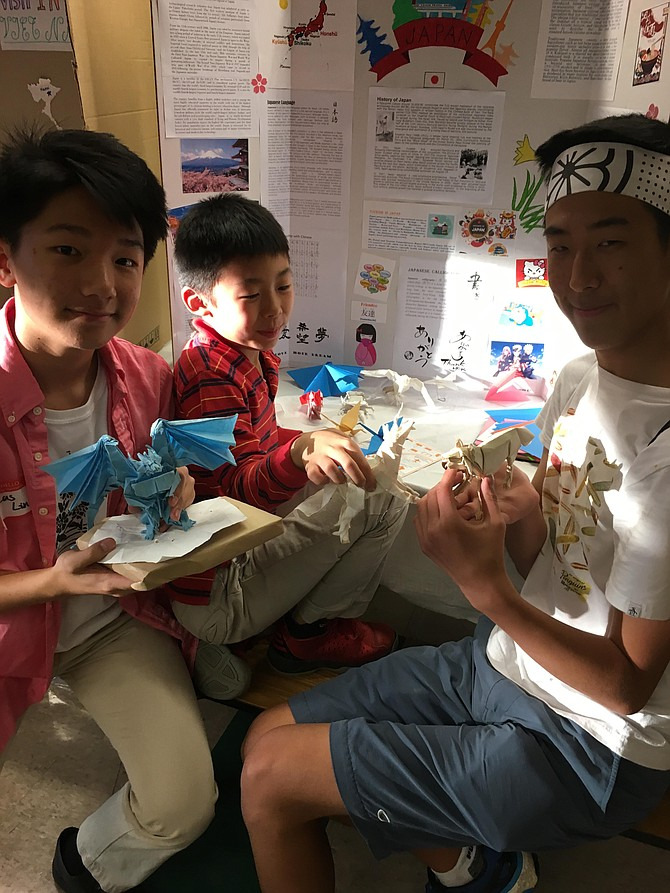 Lucas Lin, Ayden Yang and Raden Pak show off their origami creations at the Churchill High School Asian Festival Friday.
