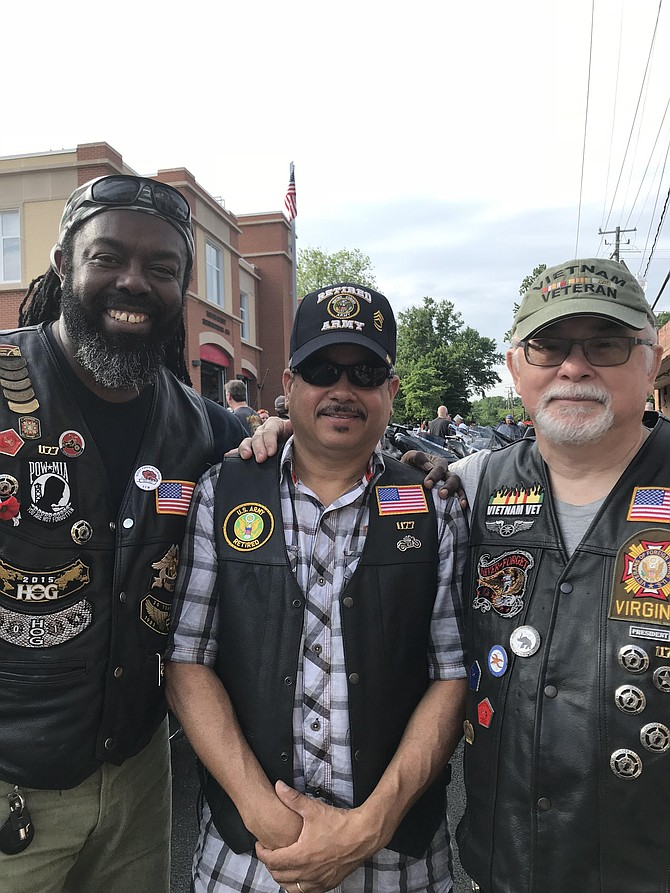 "Ray Delpesche, Commander of VFW Post 1177 Leesburg, Gene Odum, VFW Post 1177 Leesburg and Eli Contes, VFW Post 1177 Leesburg wait for the call, ""Kickstands up,""  to pull out of Herndon on the Sunday before Memorial Day. Delpesche displays the MIA/POW badge on the front of his leather. Asked what Memorial Day means to him, Delpesche requoted Robert O'Neill, ex-Navy Seal known as ""the man who killed Osama bin Laden"" and recited,   ""Memorial Day is time for reflection, pause and remembrance and thanksgiving for patriots who gave up their own lives to protect the lives and freedom of us all."""