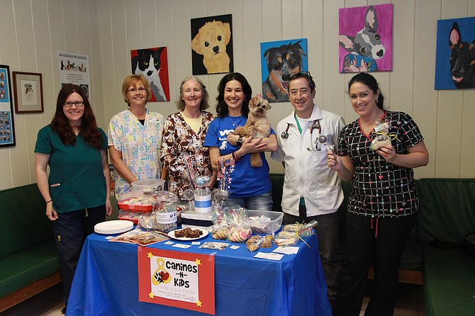 Kendra Gehringer, Christine Randall, Donna Koch, Candice Bhatia and her dog Buttercup, Eric Newhart and Sheri Virgulak as they stand behind the bake sale table at the VCA Animal Hospital.