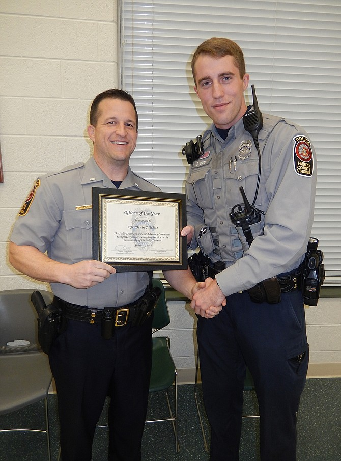 1st Lt. Ryan Morgan (left), assistant commander of the Sully District Police Station, presents Officer of the Year certificate to PFC Devin White.