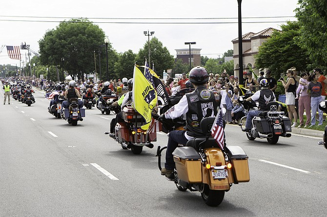 Many motorcycle riders wave flags to remember the fallen as crowds cheer them on.