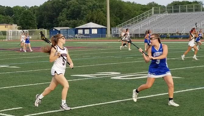 West Potomac junior Lauren McDonald, right, defends Woodson senior Logan Dougherty during Tuesday's Region 6C championship game.