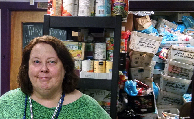 Rising Hope Food Pantry Coordinator Kathleen Simons with Stamp Out Hunger bins.