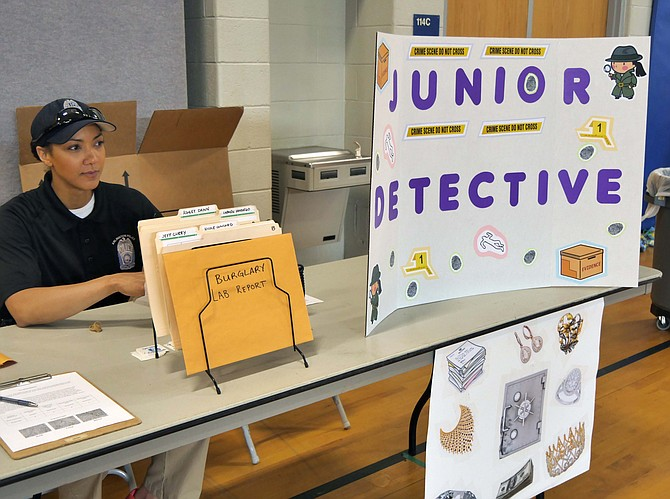 "Officer Lillian Hammond on the Arlington County Outreach Team is in charge of the Junior Detective Table. She says this is the second year for this community event. Today's crime is a burglary and the task is to find the person who committed the crime. ""You walk through the crime scene, find evidence and a fingerprint and footprint. You compare them to the possibilities."""