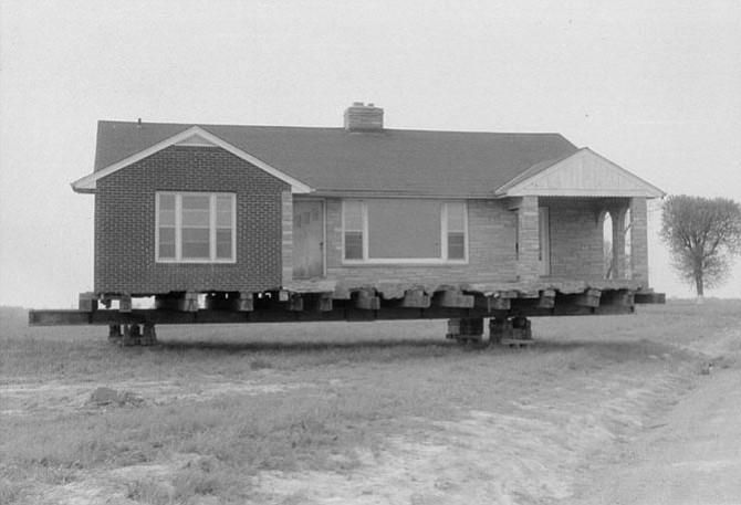 A Burke home being hauled away by a flatbed truck due to the Burke Airport.