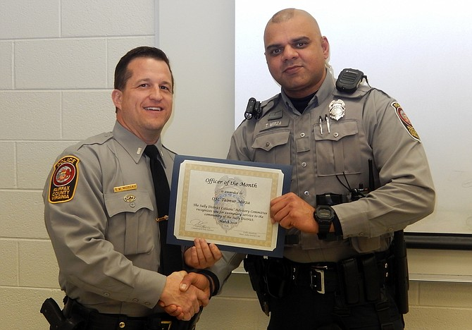 1st Lt. Ryan Morgan (left) presents the Officer of the Month certificate to Officer Taimur Mirza.