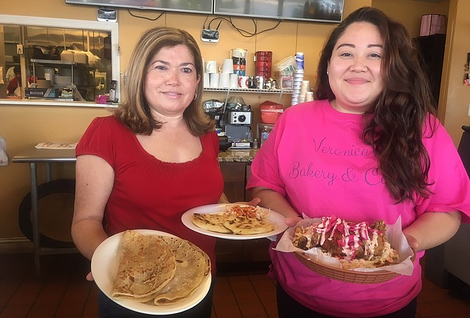 Ana Salinas with daughter Rebeca displaying their popular chicken and tortilla dish at Veronica's.