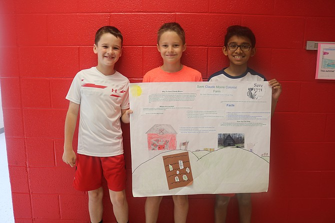 Forestville Elementary fourth graders Jack Cleveland, Evan Troy and Kriesh Tivare show the poster they made to help save the colonial farm.