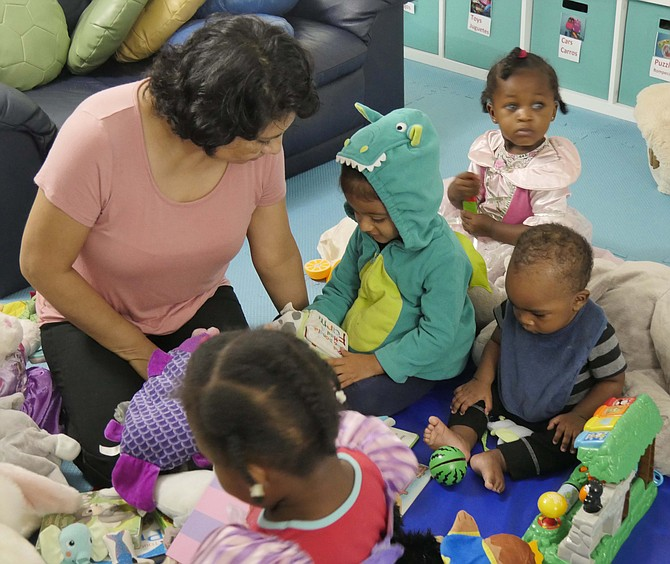 Lilia Crisostomo reads to the four children in her Campagna Center family child care home.
