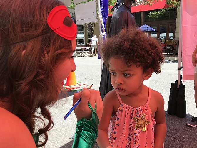 Lucia Drake, 2 1/2, seems a little shy about having her face painted by Faith Carlson, member of the Vienna Singing Princesses at Taste of Reston 2018.