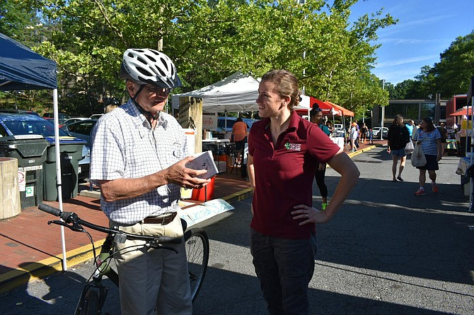 Reston resident Thomas Plevyak receives a bike map from FCDOT Bicycle Program Coordinator Nicole Wynands.