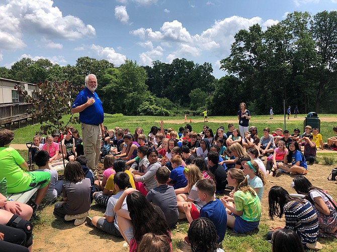 Hunter Woods, a Dominion Energy forester, tells fifth grade students at Mantua Elementary about the proper way to plant and care for a redbud tree. The students learned about the many benefits of trees through Dominion Energy's Project Plant it! program.