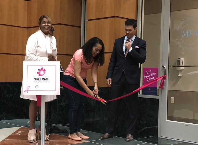 Breast cancer survivor Alessia Saunders, center, cuts the ribbon to officially open the National Breast Center June 12 in Old Town. With her are Tanya Keys of GW Medical Faculty Associates and Dr. David Weintritt, founder of the center.