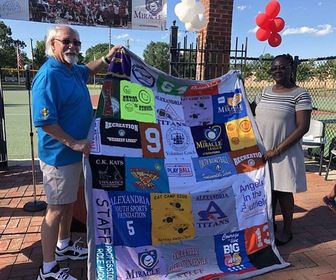Mac Slover, left, is presented a quilt by Recreation, Parks and Cultural Activities staff member Nadine Brown at a retirement celebration in his honor June 15 at the Kelley Cares Miracle Field. Brown handcrafted the quilt from Slover's old staff and recreation t-shirts representing his 30 years with the city's sports department.