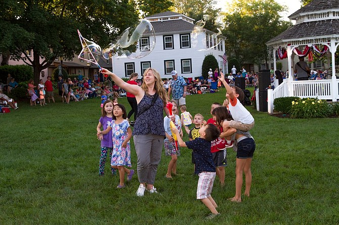 Children have fun trying to pop gigantic bubbles on the Great Falls Village Centre Green as The Alan Scott Band plays behind them.