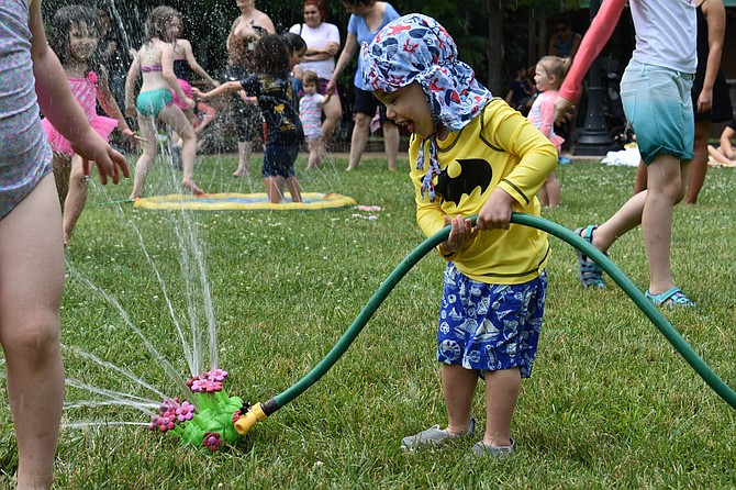 Connor Pollak, 2, plays with a flower sprinkler.