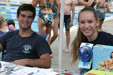 Swim-a-Thon Co-Chairs James Bouharoun, 17, and Maren Kranking, 17, work the check-in table at the event, collecting paperwork and donations to HSC Pediatric Center.