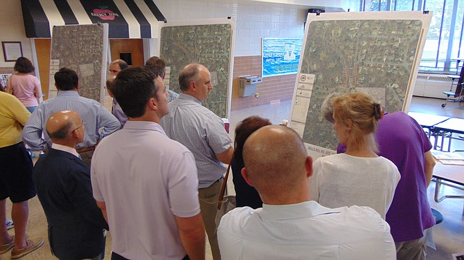 Residents look over maps showing various options to improve the Balls Hill Road and Old Dominion Drive intersection at a transportation meeting held Thursday, June 28 at Cooper Middle School.