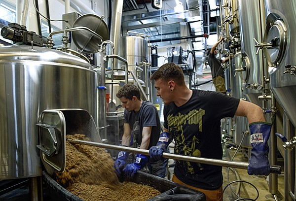 Head brewer Justin Weems and former employee Ian Gildea remove spent grain at Caboose Brewing Co. The spent grain is donated to local farms.