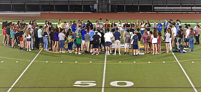 Classmates and peers participate in a vigil at Coffey Stadium in  Conner McGowan's honor, several nights after his death.