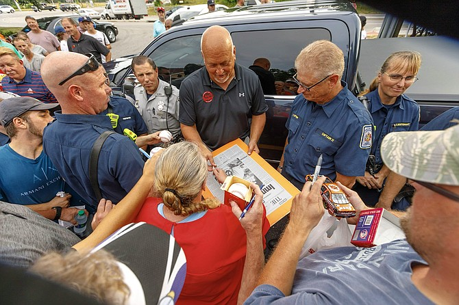 Cal Ripken Jr., center, signs a piece of memorabilia for retired Fairfax County firefighter Karrie Boswell as other police and fire personnel look on during a July 16 appearance by the baseball legend at Roy Rogers Restaurant in Alexandria celebrating the franchise's 50th anniversary.