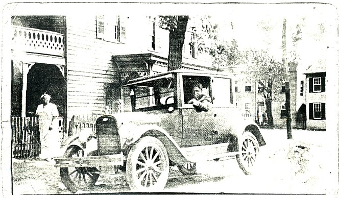 1927 picture of Charles William (CW) Gray in his car in front of his funeral business at 1021 Oronoco Street.